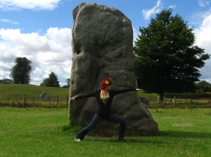 jehara doing warrior pose in front of standing stone in avebury, wiltshire, UK