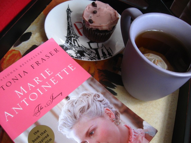 Image of MA book with a cup of tea and cupcake